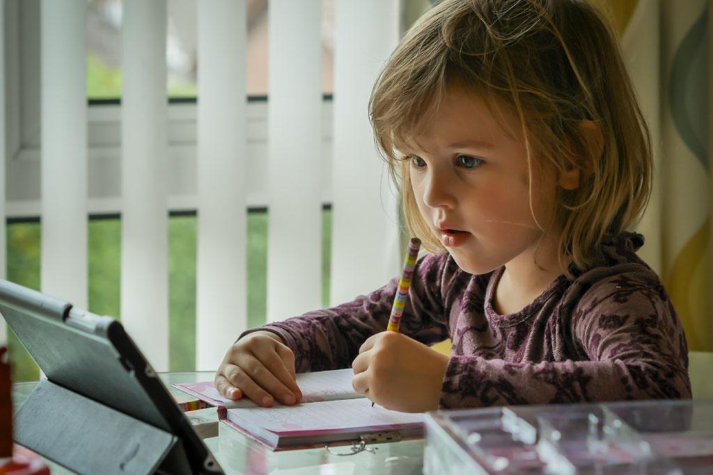 Bambina davanti al tablet mentre fa i compitini