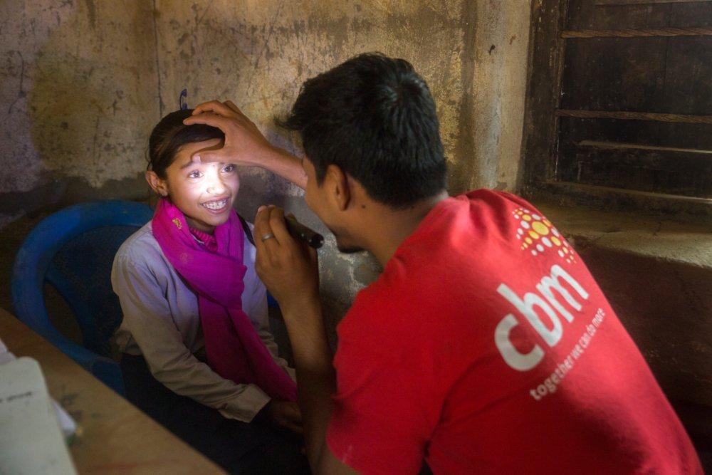 un operatore fa una visita oculista a una bambina