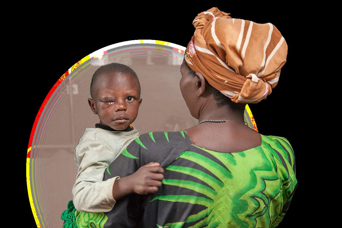 una madre di spalle tiene in braccio il suo bambino