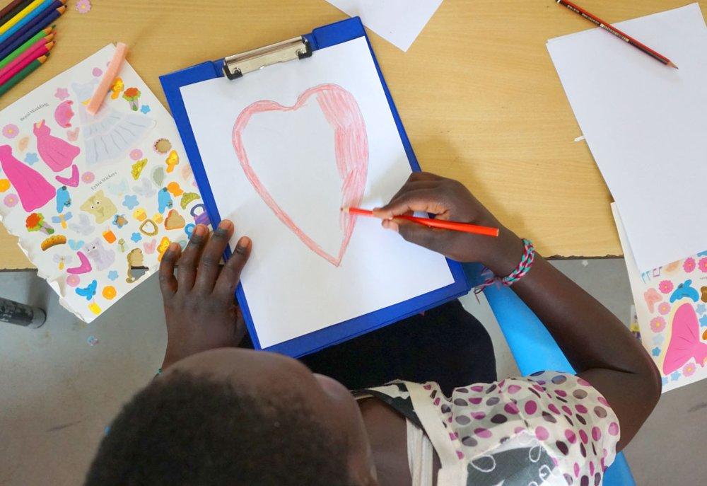 Bambina che disegna un cuore